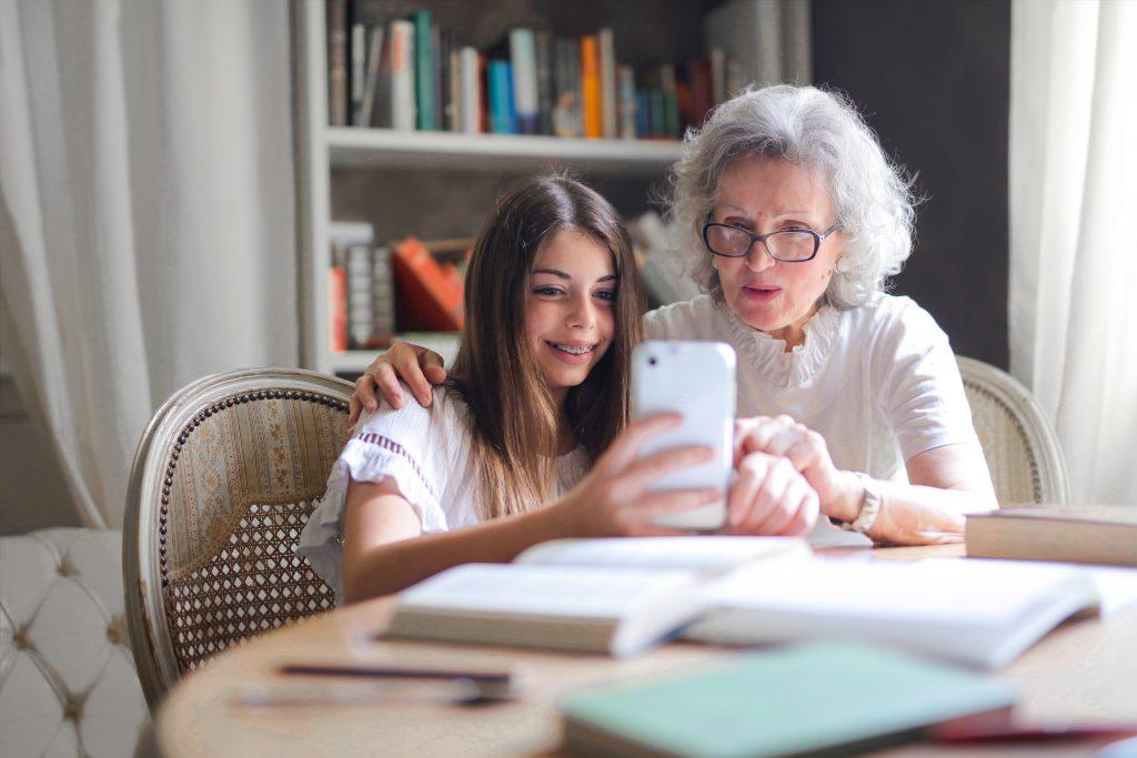 Enkelin zeigt Oma das Tablet